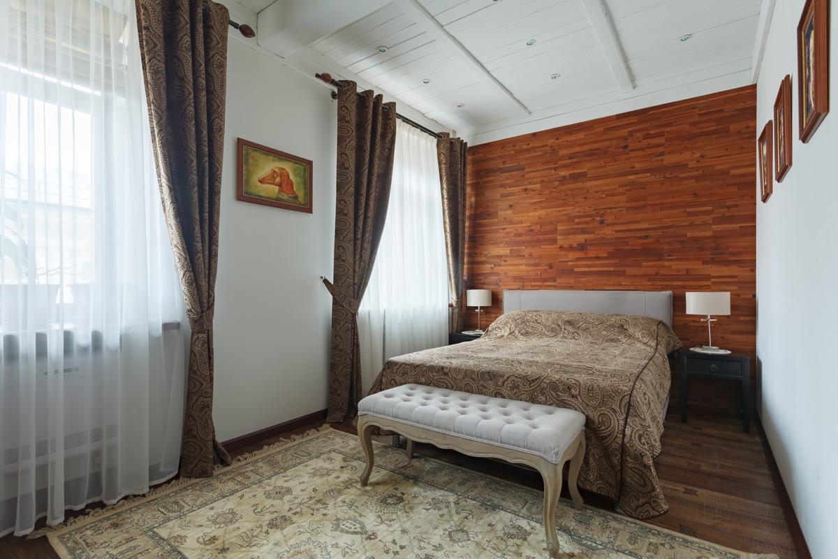 Стена за изголовьем кровати облицована деревянными панелями производства Admonder.
