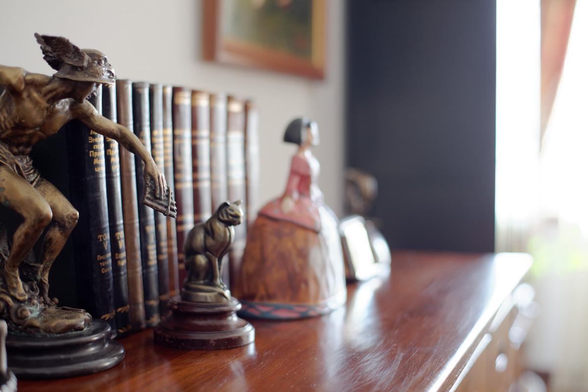 В интерьере много мелких декоративных элементов в виде всевозможных старых книг, статуэток, шкатулок и картин, которые отражают эстетические пристрастия владельца квартиры.
