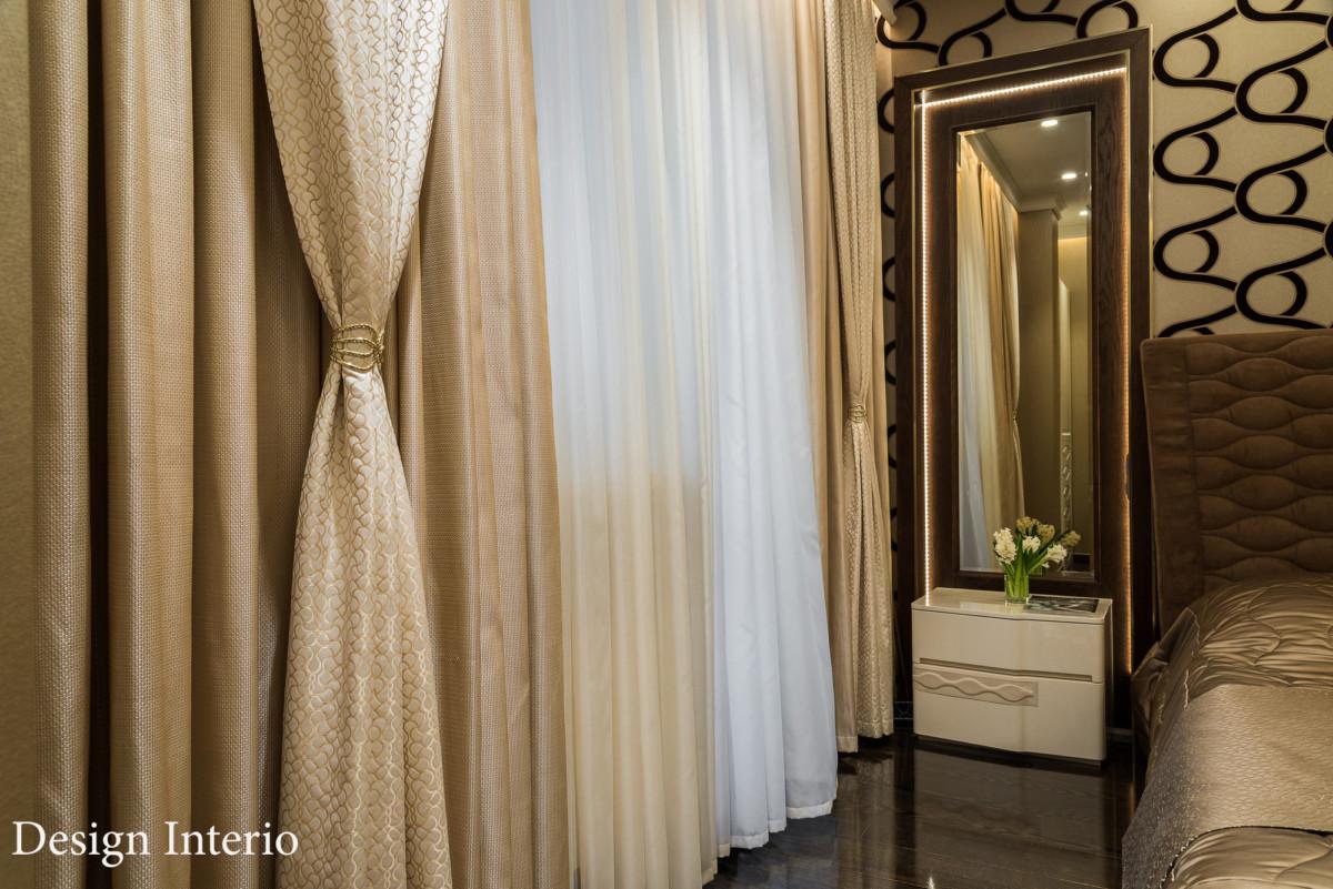 Текстиль из многослойных штор, состоящих из тюля, декоративной и основной портьеры, обрамляет окно. Металлический подхват.