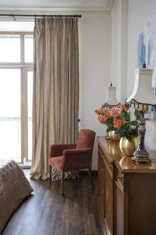 Шторы мягко лежат на полу, на комоде цветочные композиции в вазах золотистого оттенка, все приготовлено для спокойного сна и хорошего утра