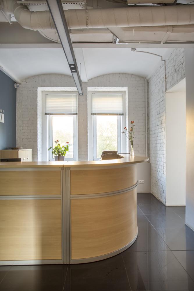 Зона ресепшен. Строгая светлая мебель в стиле минимализм приятно контрастирует с кирпичными стенами.