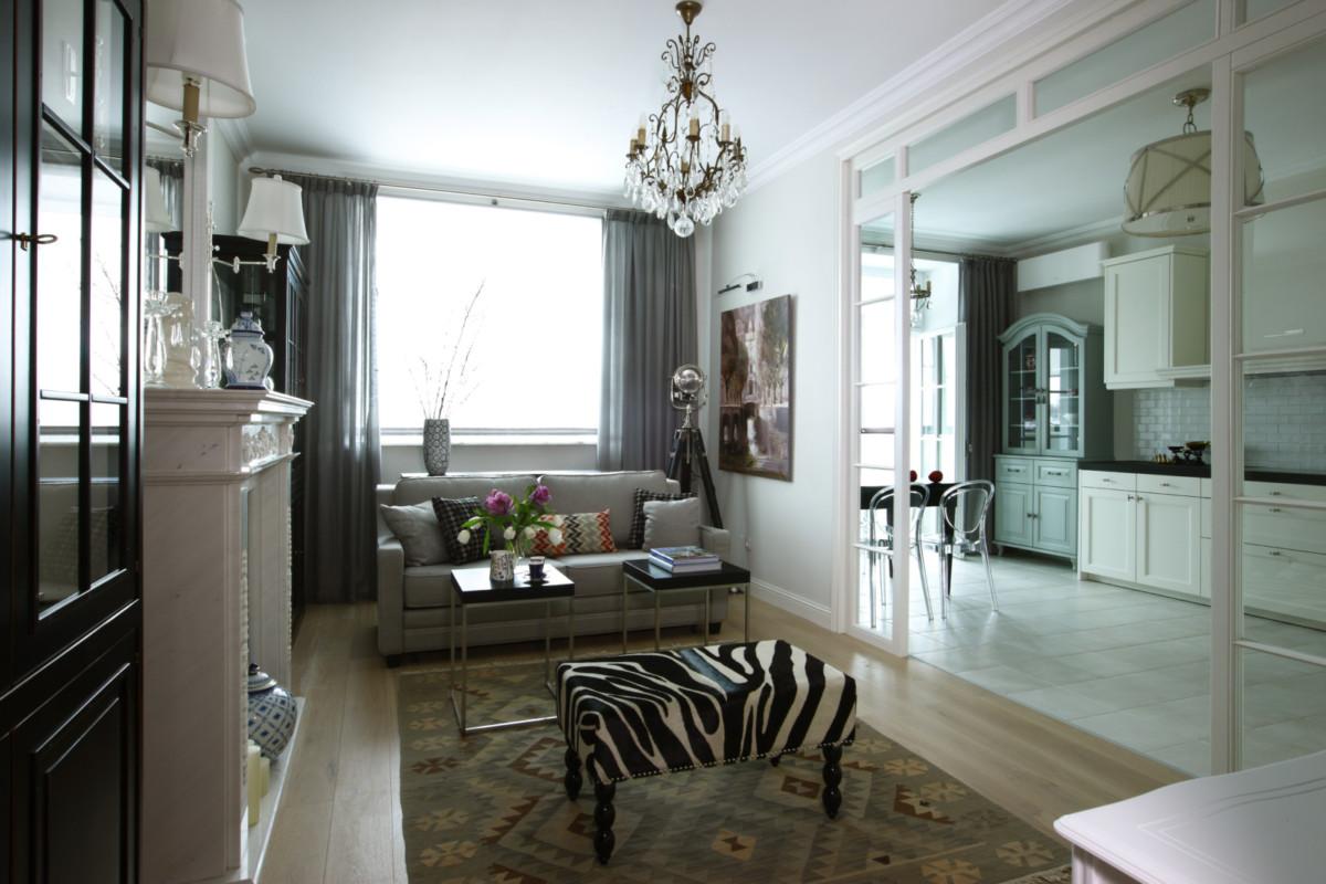 Гостиная. За лёгкой перегородкой — кухня-столовая. В гостиной в качестве ярких стилистических акцентов использованы килим и банкетка, обитая шкурой зебры.  В интерьере гостиной использована антикварная люстра и настенные светильники Ralph Lauren.